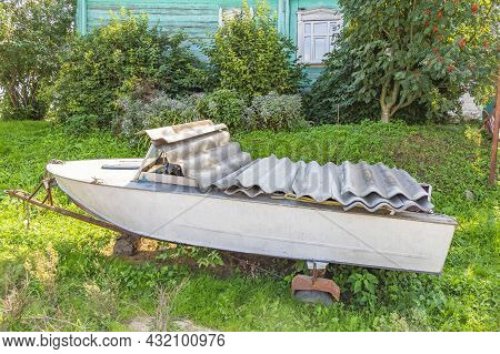 An Old Shabby Boat For Water Walks Stands In A Summer Garden Near A Weathered House