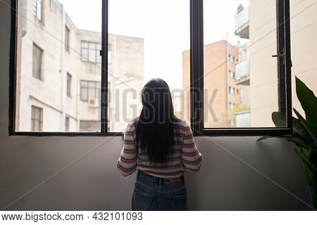 Rear View African Girl Leaning Out Of The Window, Looking Outside Where There Are Large Buildings.
