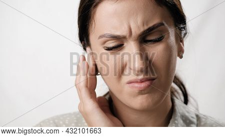 Earache. Suffering Woman On White Background With Emotions Of Pain On Her Face Touches Her Ear. Clos