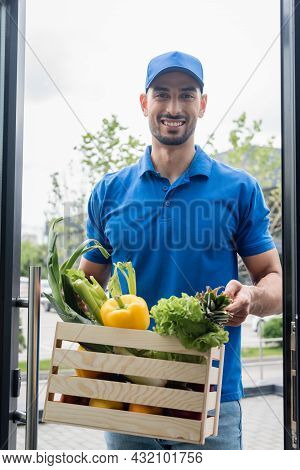 Smiling Arabian Deliveryman Holding Box With Vegetables Near Door