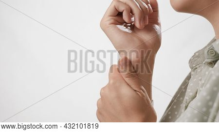 Wrist Pain. Female Hand Touches Wrist On White Background. Close-up