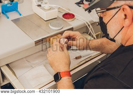 Selective Focus On The Hands Of A Male Sitting At A Workshop Table Working With A Dental Mould In A