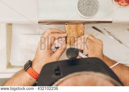 Aerial View Of A Hands Of A Man Using Wax To Mould The Pieces Of A Dental Mould In A Laboratory