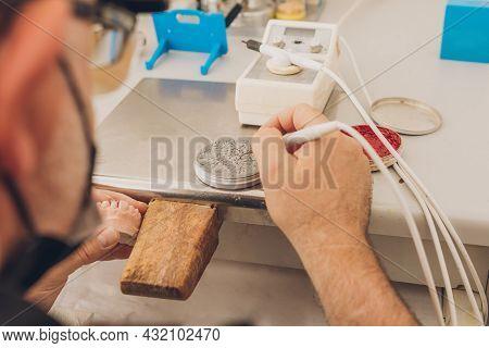 Man Using Wax To Mould A Dental Mould Sitting In A Dental Bone Ceramics Laboratory