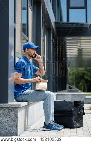 Side View Of Muslim Deliveryman Talking On Smartphone And Holding Paper Bag Near Thermo Backpack And