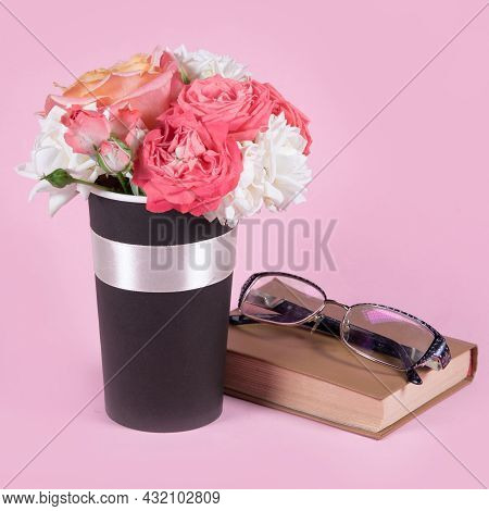 Bouquet Of Rose Flowers, Book And Glasses On Pink Background.  Copy Space