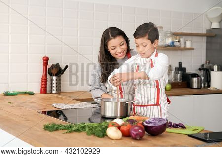 Mother Teaches Her Son To Cook Some Vegetables In The Kitchen. Lifestyle With Latin People. Child Le