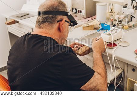 Man Sitting In A Dental Laboratory Specialising In Professional Bone-ceramic Dentistry Using Wax To