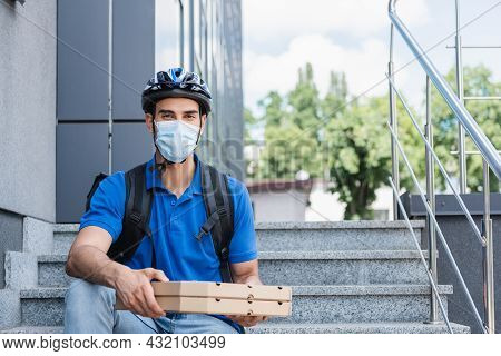 Muslim Deliveryman In Helmet And Medical Mask Holding Pizza Boxes On Stairs Of Building