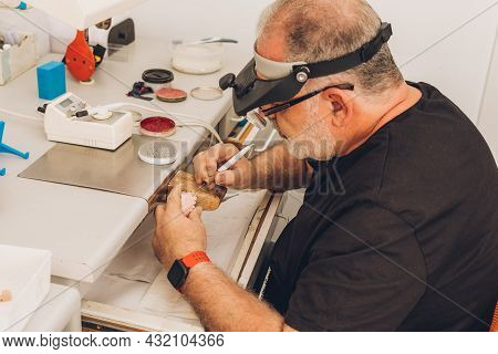 Man With Face Protections Sitting In The Workshop Of A Dental Laboratory Specialising In Dental Bone