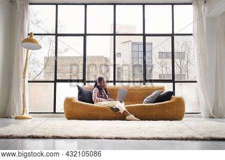 Young Woman In A Modern And Bright House, Sitting On A Sofa Using A Laptop. Student Doing Homework O