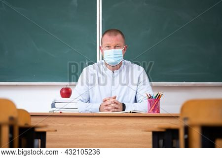 Teacher with mask in the classroom. Social distanting and classroom safety during coronavirus epidemic