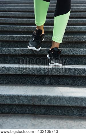Partial View Of Sportive Woman Running On Stairs Outside