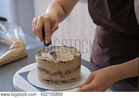 Woman Pastry Chef Lines Chocolate Cream On Chocolate Cake, Close-up. Cake Making Process, Selective