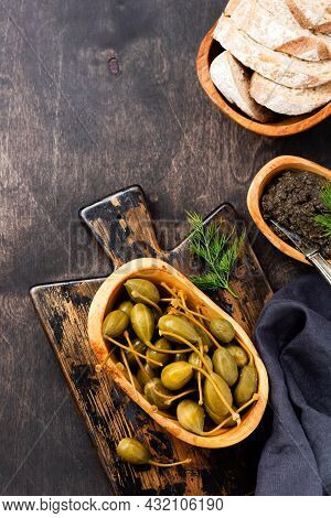 Canned Capers In Wooden Dish, Tapenade And Bread On Trendy Dark Wooden Old Background. Top View