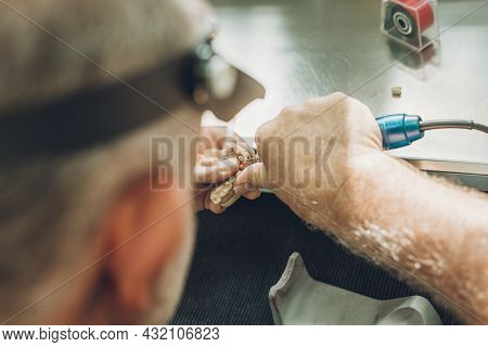 Close-up View Of A Mans Hands Adjusting A Dental Mould Using An Electric Micromotor In A Dental Labo