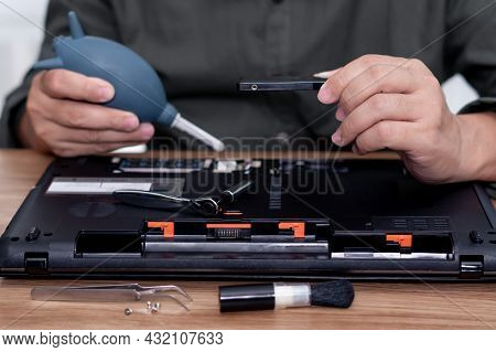 A Man Hold Hard Disk And Hand Air Pump In Repair Laptop Computer And Tool Computer Repair On The Tab