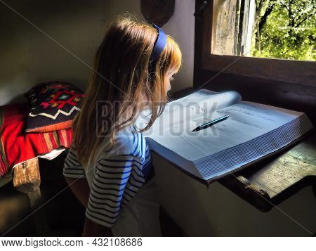 A Girl Of 8 Years Old With Long Blond Hair Near The Window Is Reading A Book. A Room With Traditiona