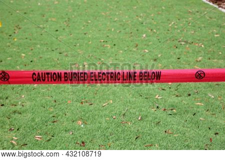 Caution Buried Electric Line Below. Caution Tape. Warning Tape. Danger Warning Tape. Electrical Lines Buried Under Ground. Electricity Hazard. Red Warning Caution Tape.