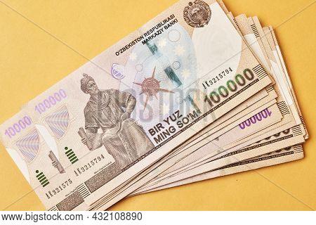 Pile Of Uzbek Sums On Yellow. Uzbek Currency Money Bill. A Stack Of One Hundred Thousand Uzbek Sum.