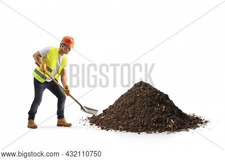 Construction worker with a vest and hardhat digging earth with a shovel isolated on white background
