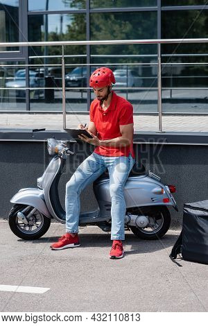 Young Muslim Deliveryman Writing On Clipboard On Scooter Near Thermo Backpack Outdoors