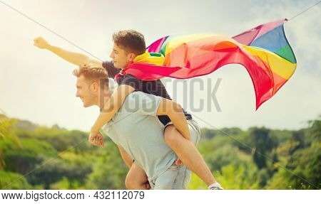 Happy young couple, gay family with flying LGBT rainbow flag having fun outdoors. Joyful gay men together in a park. laughing, hugging, enjoying nature outside, over sunny sky. Super hero. Piggyback.