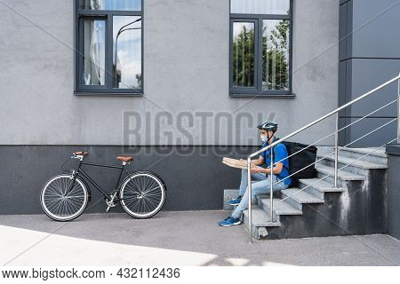 Arabian Deliveryman In Medical Mask Holding Pizza Boxes Near Bike And Building Outdoors