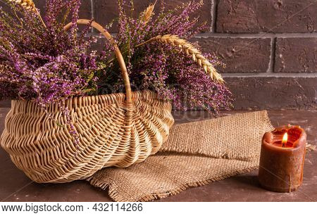 Basket With Flowers On A Brown Background, Lilac Heather And Atmospheric Candle, Copy Space