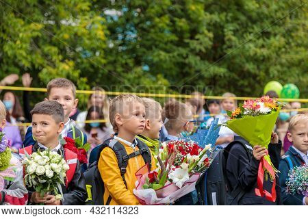 First Graders Walk With Bouquets On September 1. Children Go To School, First Grade With Flowers.