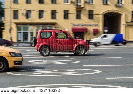 Red Suzuki Jimny Car Moving On The Street On High Speed. Side View Of Compact Suv In Motion. Moscow,