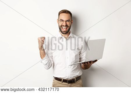 Business. Happy Manager Winning Online, Rejoicing With Fist Pump, Holding Laptop And Triumphing, Sta