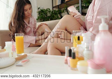 Beautiful Young Women In Silk Pajamas Applying Moisturizing Lotion On Legs To Keep Skin Moisturized