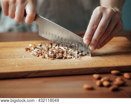 Female Hands Chopping Almonds. Close Up Shot Of Process Crushing Raw Unroasted Almonds With Large Kn