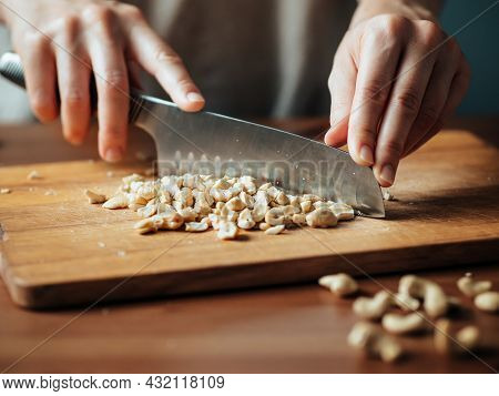 Female Hands Chopping Cashew. Close Up Shot Of Process Crushing Raw Unroasted Cashew With Large Knif