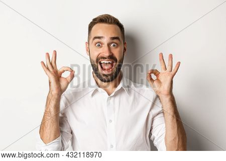 Close-up Of Amazed Caucasian Guy Agreeing, Showing Okay Signs And Looking Impressed, Recommending Pr