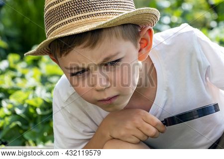 Serious Adorable Little Child Boy In Straw Hat With Magnifying Glass Watching Or Looking For. Kid Co