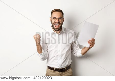 Successful Manager Making Fist Pump, Rejoicing Of Work And Showing Documents, Standing Over White Ba