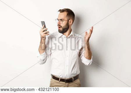 Man Looking Confused At Mobile Phone After Conversation, Standing Puzzled Over White Background