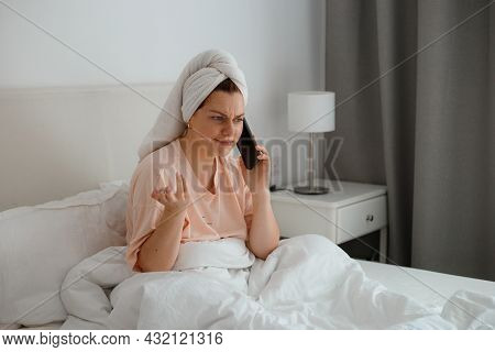 Happy Young Caucasian Woman Relax On Comfortable Bed At Home And Use Cellphone, Talk With Boyfriend.