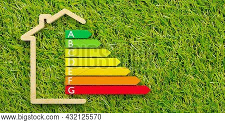 European Energy Classification Label In Wooden House Outline Shape On Grass Background, Energy Consu