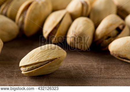 Close Up Of Single Pistachio In Front Of Heap Of Salted, Roasted Green Pistachio Nuts Snack Over Woo