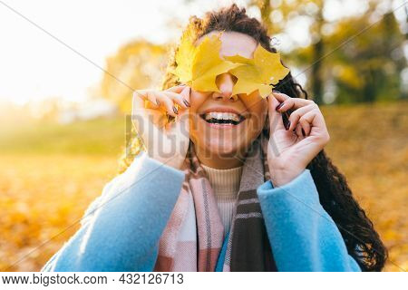 Young Beautiful Woman Have Fun With Yellow Autumn Leaves In The Park On A Warm Autumn Day