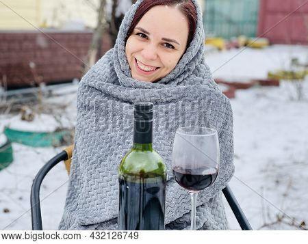 Young Woman Sitting In Yard And Drinking Red Wine In Snowy Weather. Female Wrapped In Grey Plaid Sit