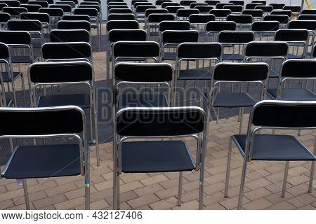 Rows Of Chairs In The Stadium. Black Empty Seats Outdoors. Lecture, Concert, Open-air Cinema, Busine