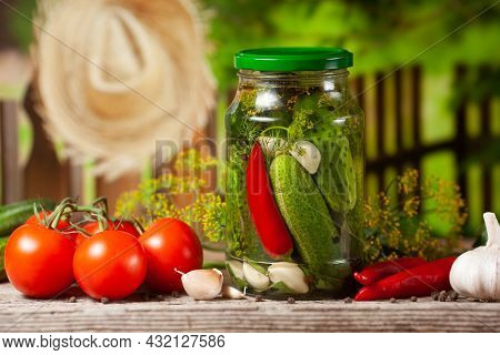 Pickled Cucumbers In Glass Jars And And Vegetables For Preparation Of Pickles On Background Of Fence