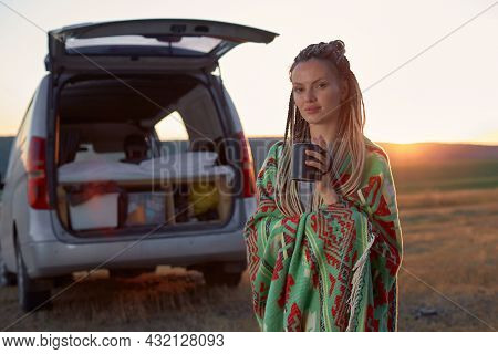 A Hippie Woman In A Bright Ethnic Blanket Holds A Mug Standing In A Field At Sunset, Near Her Car. H