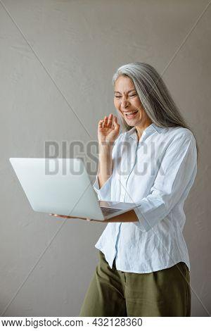 Joyful Mature Asian Woman Laughs Communicating At Videocall Via Laptop In Studio