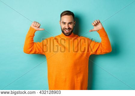 Handsome Confident Man Pointing At Himself, Looking Self-assured, Standing In Orange Sweater Against