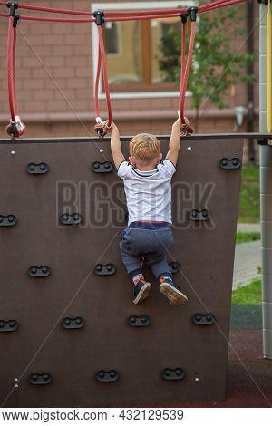Caucasian Boy Climb The Climbing Wall In The Playground